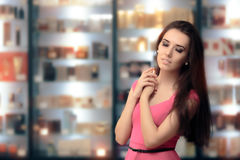 Beautiful Girl Testing Perfume in a Cosmetics Shop. Shopping woman looking for the best scent in a perfumery Royalty Free Stock Photography
