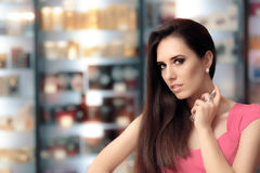Beautiful Girl Testing Perfume in a Cosmetics Shop. Shopping woman looking for the best scent in a perfumery Royalty Free Stock Photo