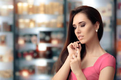Beautiful Girl Testing Perfume in a Cosmetics Shop. Shopping woman looking for the best scent in a perfumery Stock Image
