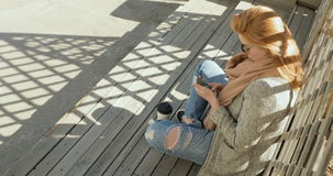 Beautiful girl texting on smartphone in the city. Beautiful red head girl texting on smartphone in the city, Sits on the steps stock video footage