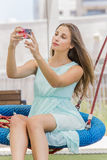 Beautiful girl texting and taking self picture on the park Stock Photos
