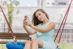 Beautiful girl texting and taking self picture on the park Royalty Free Stock Photos