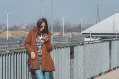 Beautiful girl texting in an urban context Royalty Free Stock Images