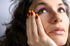 Beautiful girl thinking. Beautiful girl with colorful nails and make up, thinking Stock Photography