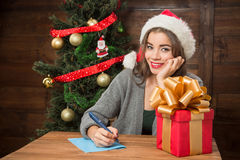 Beautiful girl thinking about New Year and Christmas congratulation. Happy beautiful girl smiling and thinking about New Year and Christmas congratulation to Royalty Free Stock Images