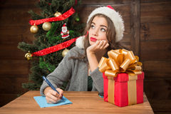 Beautiful girl thinking about New Year and Christmas congratulation. Serious lady thinking about New Year and Christmas congratulation and looking away while Royalty Free Stock Photo