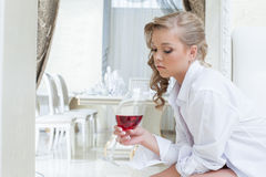 Beautiful girl thoughtfully looks at glass of wine Royalty Free Stock Image