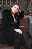 Beautiful girl thoughtfully sitting on the bench Stock Images