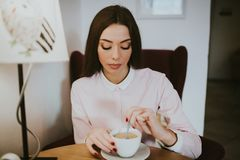Beautiful girl thoughtfully drinks coffee in the cafe. Beautiful girl thoughtfully stirs a spoon of coffee in a cafe. She is dressed in a pink shirt, next to her royalty free stock photos