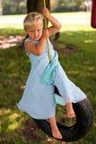 Beautiful girl on tire swing stock photo