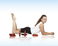 Beautiful girl to lie near by dumbbell Stock Photos