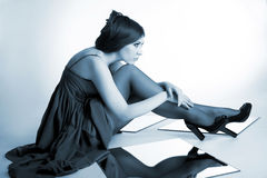 Beautiful girl toned blue. Beautiful girl sitting on the floor Royalty Free Stock Photography