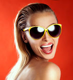 Beautiful girl with toothy smile. Portrait of happy smiling blonde woman wearing fashionable sunglasses, looking at camera. Beautiful girl with toothy smile Royalty Free Stock Photography