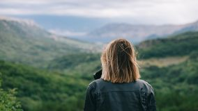 Beautiful girl on top of mountain watching scenery. Rear view of traveller woman stock photography