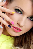 Beautiful girl touch her face with colored fingers Stock Photography
