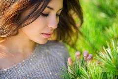 Beautiful girl touches needles on the spruce. Beautiful brunette touches needles on the spruce. Close-up. Shallow depth of field royalty free stock photos