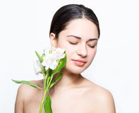 Beautiful girl touching her cheeks to flower during spa Royalty Free Stock Photos