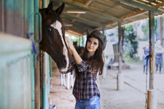 Beautiful girl touching horse Royalty Free Stock Images