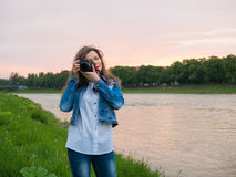Beautiful girl tourist in a cotton jacket taking photos with a professional camera on the banks of the river in windy weather.  Royalty Free Stock Image