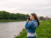 Beautiful girl tourist in a cotton jacket taking photos with a professional camera on the banks of the river in windy weather.  Stock Image