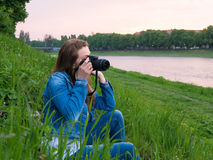 Beautiful girl tourist in a cotton jacket taking photos with a professional camera on the banks of the river in windy weather.  Royalty Free Stock Images