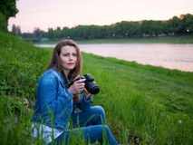 Beautiful girl tourist in a cotton jacket taking photos with a professional camera on the banks of the river in windy weather.  Royalty Free Stock Photo