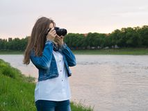 Beautiful girl tourist in a cotton jacket taking photos with a professional camera on the banks of the river in windy weather.  Stock Images