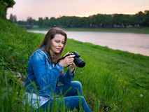 Beautiful girl tourist in a cotton jacket taking photos with a professional camera on the banks of the river in windy weather Royalty Free Stock Photo