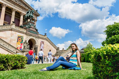 Beautiful girl tourist on the lawn outside the museum in Berlin, on a sunny day Stock Photos