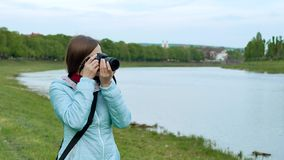 Beautiful girl tourist taking photos with a professional camera on the banks of the river. stock footage