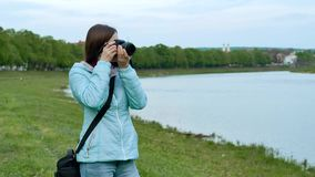 Beautiful girl tourist taking photos with a professional camera on the banks of the river. stock video
