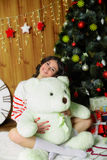 Beautiful girl with toy bear at Christmas tree Stock Photo