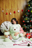 Beautiful girl with toy bear at Christmas tree Stock Image