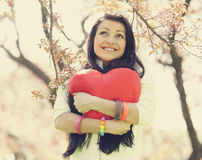 Beautiful girl with toy heart in spring park Royalty Free Stock Image