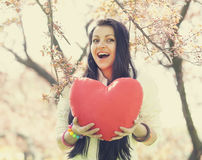 Beautiful girl with toy heart in spring park Stock Photo