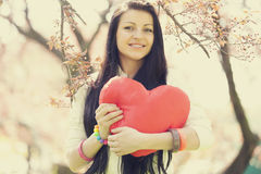 Beautiful girl with toy heart in spring park Stock Image