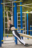 Beautiful girl in a tracksuit on the Playground deals with rings. Girl exercising on the rings in a tracksuit and on the Playground Stock Photography