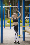 Beautiful girl in a tracksuit on the Playground deals with rings Stock Photography