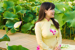 Beautiful Girl in tradition dress plays in the lotus garden stock images