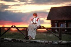 A beautiful girl in a traditional Russian dress is sitting on a fence against the sunset