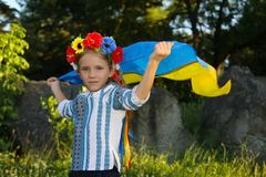 Beautiful girl in traditional Ukrainian clothes holding a flag of ukraine. At summer day stock images