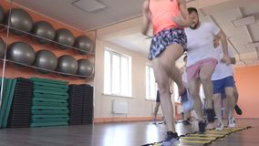 Beautiful girl trainer at a group lesson in a modern fitness center shows caucasian men exercises to lose weight. Healthy lifestyle stock video footage