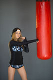 Beautiful girl in training. Beautiful slender girl in a sport dress beats a punching bag Royalty Free Stock Photography
