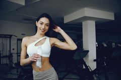 Beautiful and elegant girl standing in a gym royalty free stock photography