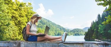 Beautiful girl traveler in a hat on a lake with a laptop Work outside the office. Banner royalty free stock image