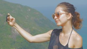 Beautiful girl traveler is taking a selfie with sea view at a height in slowmo. Beautiful girl traveler is taking a selfie with sea view at a height. slow motion stock video footage