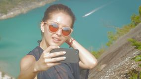 Beautiful girl traveler is taking a selfie with sea view at a height in slowmo. Beautiful girl traveler is taking a selfie with sea view at a height. slow motion stock footage