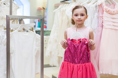 Beautiful girl tries on a festive red dress in the store Stock Photo