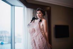 Beautiful girl tries on a pink wedding dress stock photos