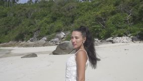 Beautiful girl on tropical island. Beautiful brunette woman in white dress looking into the camera while standing on the tropical paradise island beach - video stock video footage